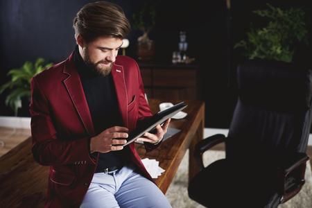 デジタル タブレットの自宅と事務所を働いていた男に焦点を当ててください。 写真素材