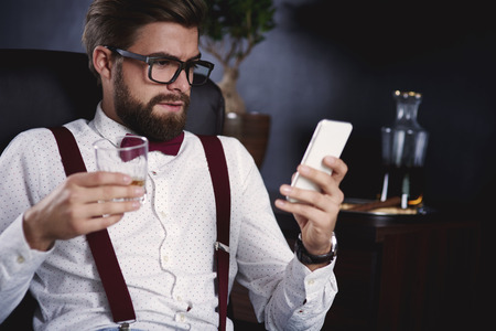 Businessman using his smartphone and drinking tea