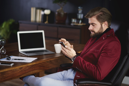 Businessman using his a mobilephone at home office Banco de Imagens