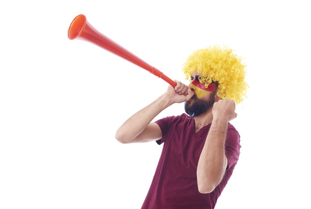 Soccer fan with wig and vuvuzela celebrating   Stock Photo