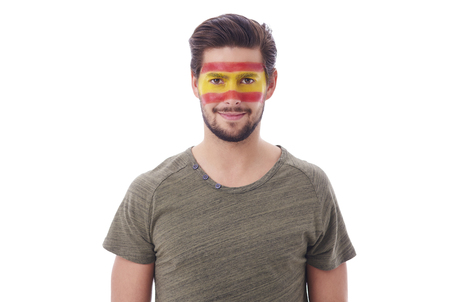 Portrait of cheerful man with spanish flag on face