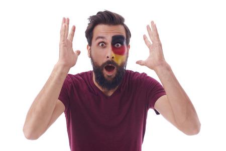 Geschokte Duitse voetbalfan kijken naar voetbalwedstrijd in ongeloof