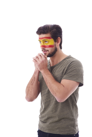 Side view of nervous fan with spain flag on face praying