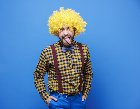 Man with wig sticking tongue out