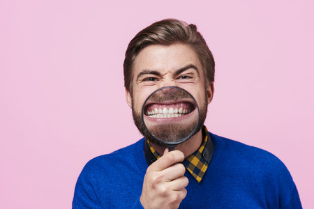 Man holding magnifying glass against open mouth