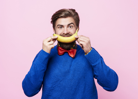 Man holding a banana in front of his  mouth