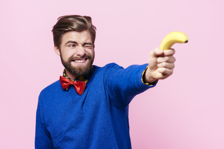 Man holding banana as a gun
