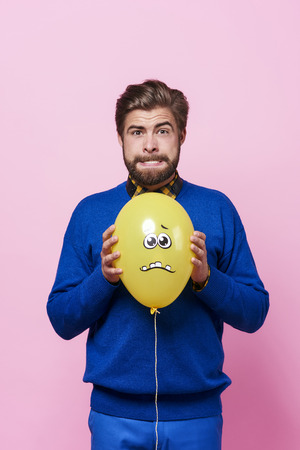 Angry man trying to squeeze a balloon   Stock Photo