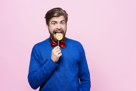 Man licking a lollipop at studio shot Stock Photo