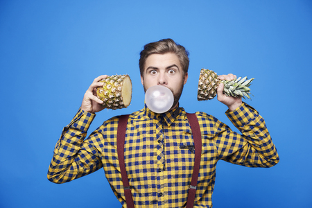 Frightened man posing with chewing gum and fruit  Banco de Imagens