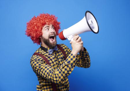 Vrolijke kerel met pruik die in megafoon schreeuwt Stockfoto