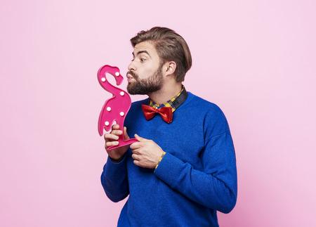 Playful man kissing artificial a  flamingo   Reklamní fotografie