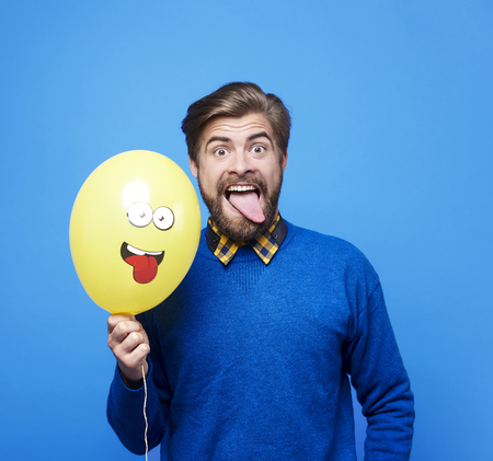 Man with balloon sticking his tongue out