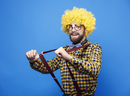 Man with wig pulling suspenders Stock Photo