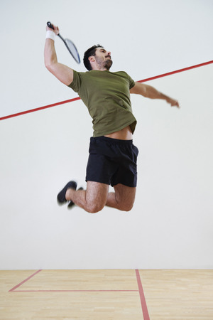 Male player jumping to hit a ball during squash match