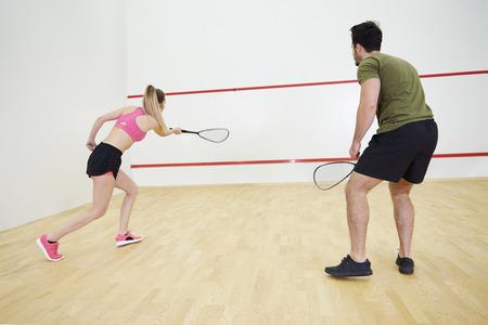 Man and woman playing squash