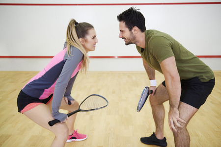 Cheerful man and woman starting squash game  Stock Photo