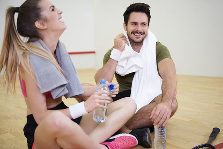 Squash players with towel resting and drinking water on floor