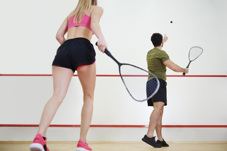 Rear view of man and woman playing squash together  Stock Photo