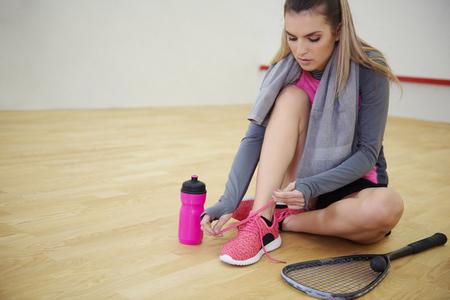 Squash player tying sports shoe