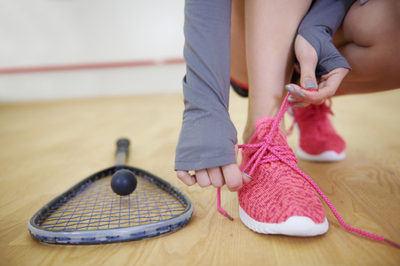 Female squash player tying sports shoe