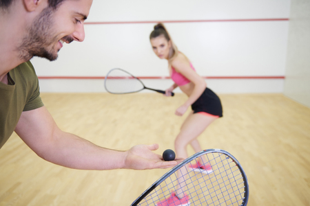 Couple playing squash at court