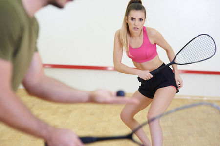 Friends playing squash at court  Stock Photo