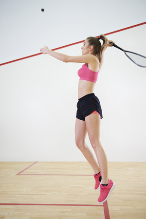 Woman jumping to hit a ball during squash game