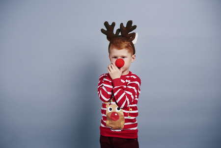Boy with reindeer antlers and red nose Фото со стока
