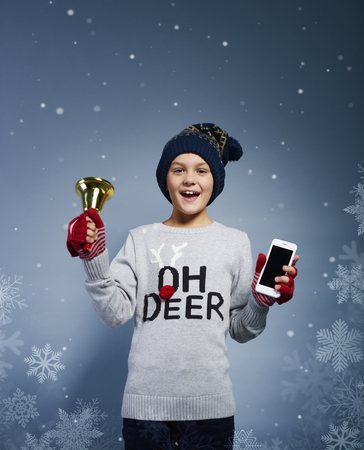Boy with christmas bell and mobile phone