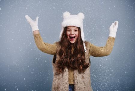 Cheerful girl among snow falling   Foto de archivo
