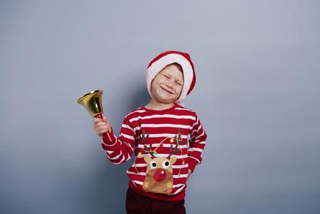 Cheerful boy with handbell at studio shot   Stock Photo