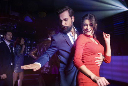 Embraced couple dancing at night club  Banco de Imagens
