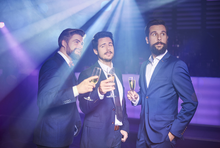 Three gentlemans in suit at night club