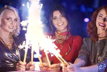 Smiling women holding sparklers at night   Stock Photo