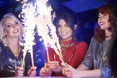 Happy woman holding burning sparklers Stock Photo