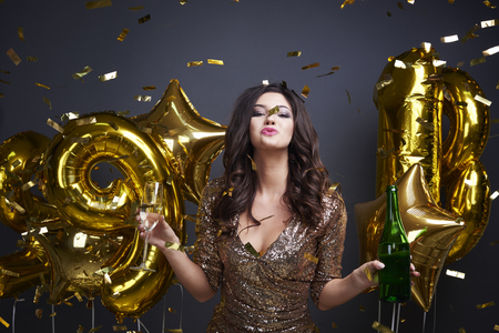 Cheerful woman with alcohol celebrating new years eve