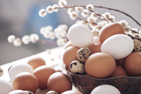 Different kind of eggs in basket on table