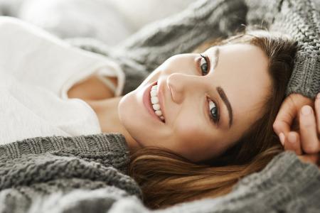 ベッドでリラックスする陽気な女性