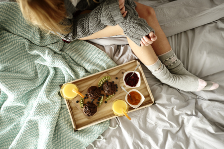 Unrecognizable woman and breakfast on bed Stock Photo - 93446127