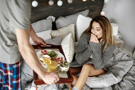 Man bringing surprised woman breakfast