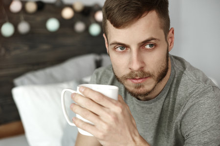 Thoughtful man drinking morning coffee