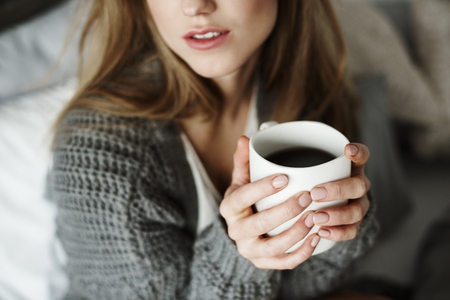 Unrecognizable woman with coffee mug on bed Reklamní fotografie