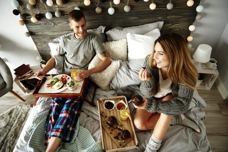 男と女のベッドで朝食を食べる