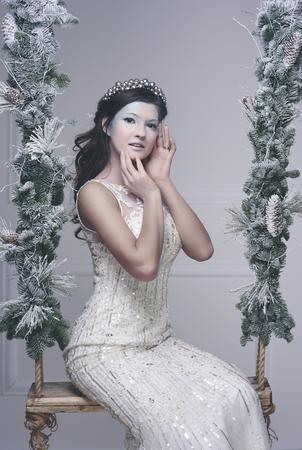 ブランコに王冠を持つ雪の乙女 写真素材