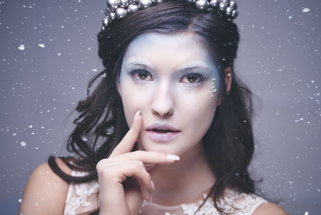 Attractive snow queen among snow falling    写真素材