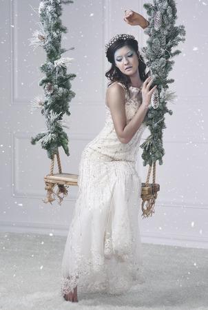 Shot of attractive ice queen on swing  Imagens