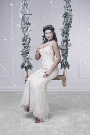 Snow queen on swing at studio shot  Imagens
