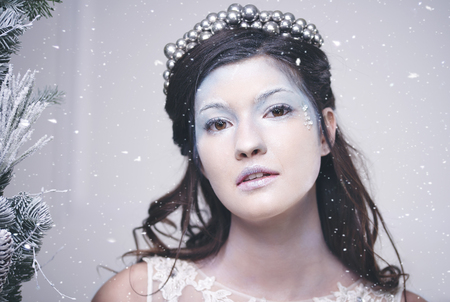 Portrait of beautiful snow queen among falling snow Stock Photo