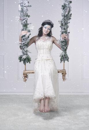ブランコに雪の女王の衣装を着た女性 写真素材